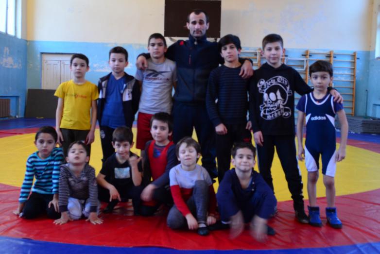 Тренер по вольной борьбе Ахра Цвижба с юными спортсменами на соревнованиях