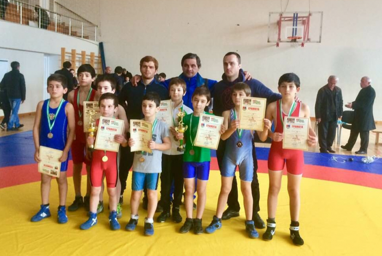 Freestyle wrestling coach Akhra Tsvizhba with young athletes at competitions