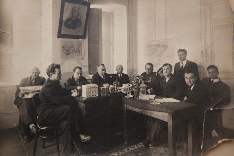 من اليمين إلى اليسار: يقف إيفان أدجينجال، مجهولان، أندريه تشوتشوا، ديرميت جوليا، ليف سولوفيوف، كونستانتين شاكريل، فاسيلي (ميشا) معان، ألفريد كولاكوفسكي (عالم نبات)، غير معروف - سوخوم، معهد اللغة والتاريخ باسم الاكاديمي ماررا 1939- 1941