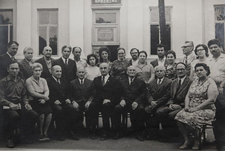 فريق من العلماء من معهد الدراسات العلمية الأبخازي، من اليسار إلى اليمين: سيرغي زوخبا، ليلي شامبا أكابا،غير معروف، أرفيلود كوبرافا، غيورغي دزيدزاريا (في الوسط)، كونستانتين شاكريل، أكيبي خونيليا، ليو شيرفاشيدزه، غير معروف ؛ الوقوف من اليسار إلى اليمين: شوتا سالاكايا، أليكسي ميخائيلوفيتش ميكفابيا، غير معروف، باجغور ساجاريا، رومان تشانبا، إيلينا مارجانيا، غير معروف، ليودميلا خروشكوفا (عالمة آثار)، فلاديمير دارساليا، ليديا تشكادوا، فلاديمير تسفينيا، فلاديمير تسفيناريا، غير معروف سوخوم، 1974