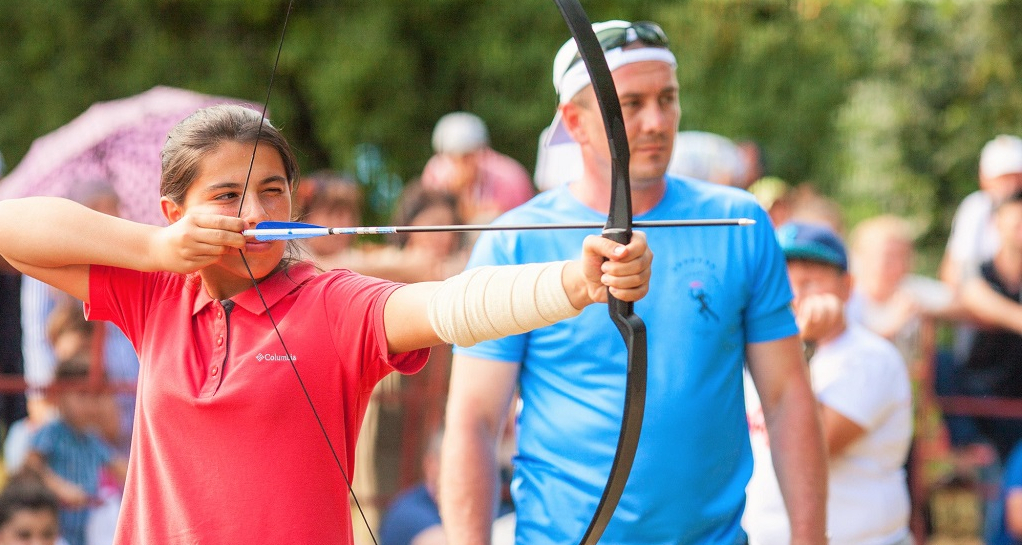 The young Abazin girl shoots a bow under close supervision of her mentor. Archery is traditionally represented in the Abkhaz-Abaza games.