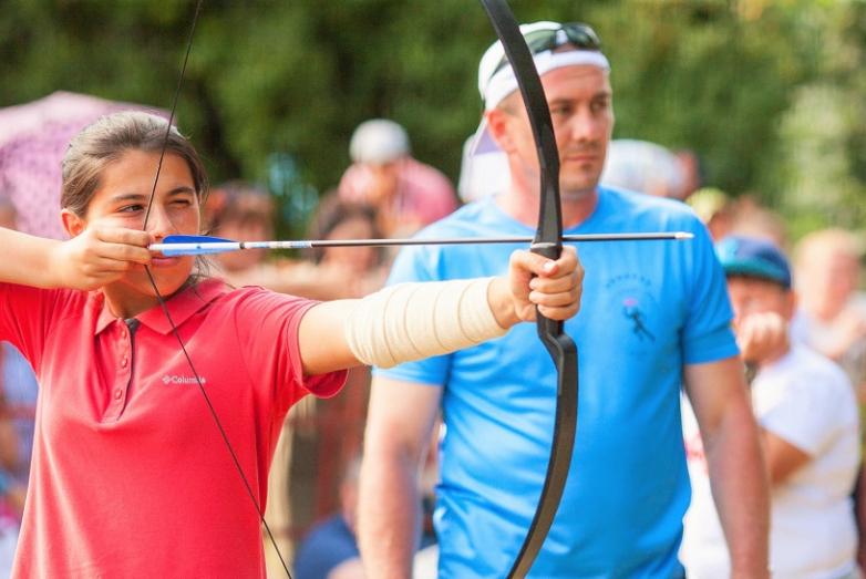 Юная абазинка под пристальным контролем своего наставника стреляет из лука по мишени. Стрельба из лука традиционно представлена на абхазо-абазинских играх.