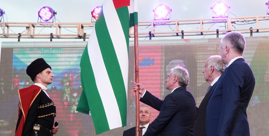 The chief of the Guard of Honor Company passes the state flag to the President of Abkhazia Raul Khadzhimba.