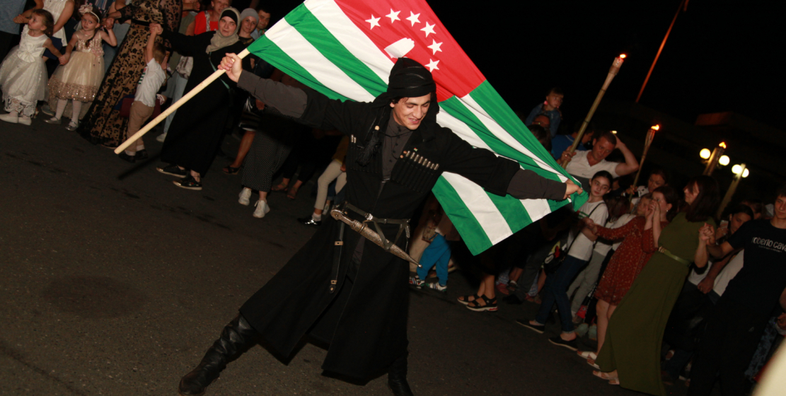A young Abkhaz in national costume with the Abkhaz flag in his hands performs folk Abkhaz dance surrounded by other participants of the festive event