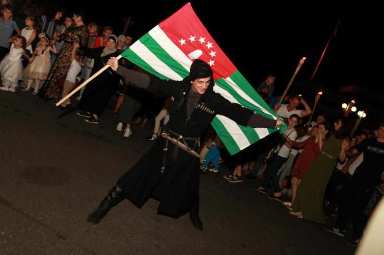 Молодой абхаз в национальном костюме с абхазским флагом в руках исполняет народны абхазский танец в окружении других участников праздничного мероприятия