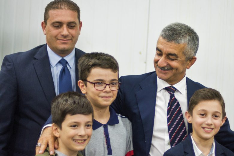 "Member of the Presidium of the WAC Anuar Abaza (Chkua) and Mussa Ekzekov with children from the Abkhaz-Abaza Diaspora in the office of the public organization ""Diwan Abaza"""