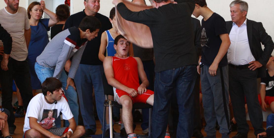 Гости турнира поддерживают молодого спортсмена, который только что завершил бой.