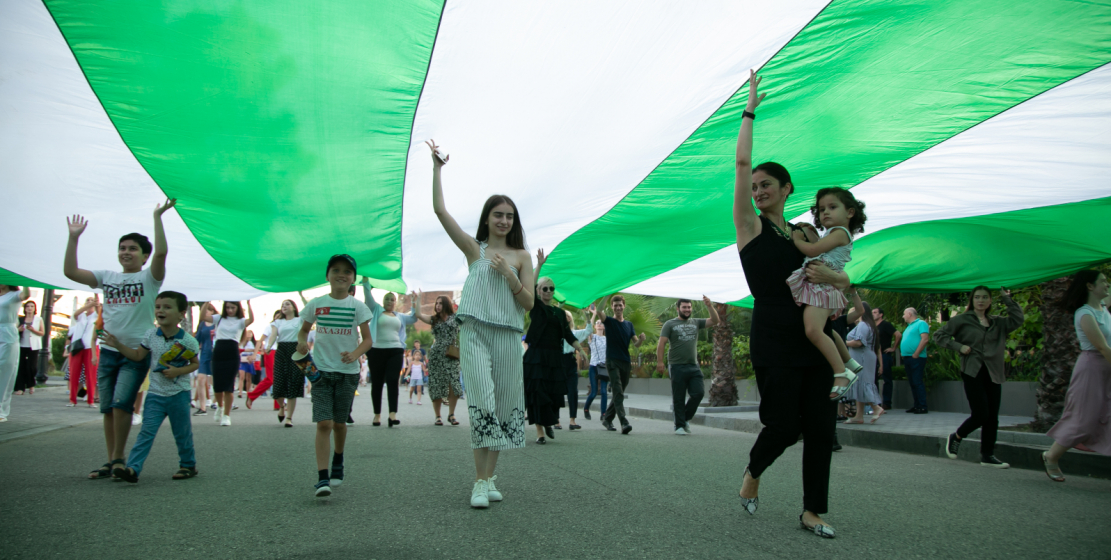 A huge canvas of the State Flag of Abkhazia was carried by both children and adults.