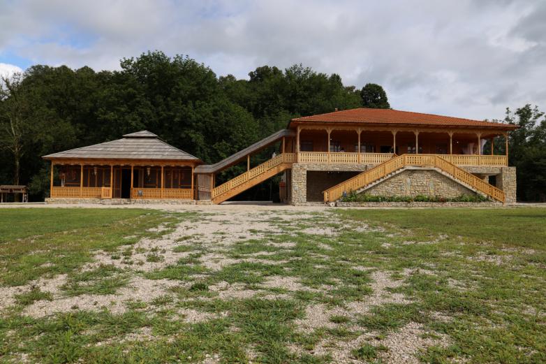 На фото: двор традиционной абхазской усадьбы с ухоженной травой и традиционными абхазскими строениями.